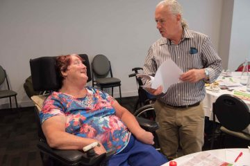 Advocate helping to speak on behalf of lady in wheelchair