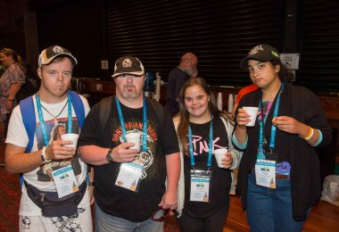 group of 4 people attending event and drinking coffee